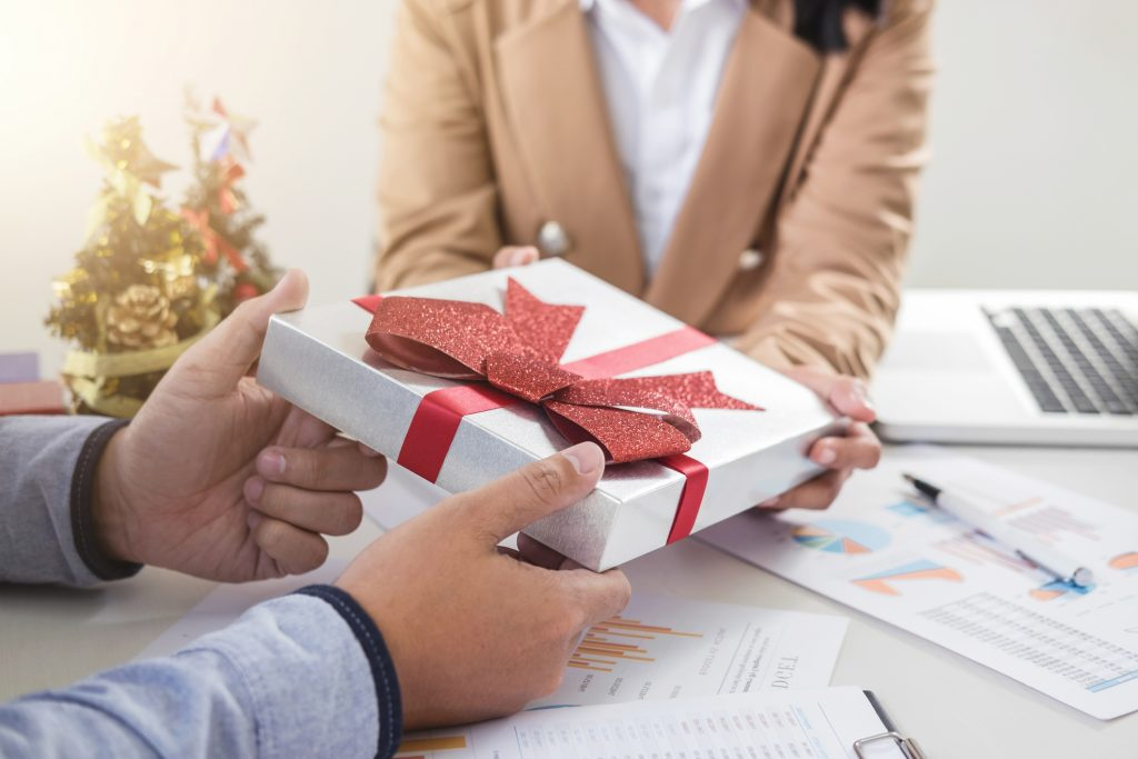 Businesswoman Giving Christmas Gift To Colleague At Desk In Office